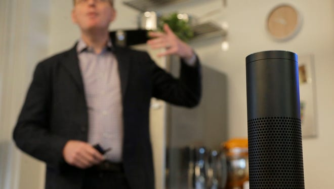 In this March 2, 2016 photo, David Limp, Amazon Senior Vice President of Devices, center, speaks behind an Amazon Echo in San Francisco. Amazon.com is introducing two devices, the Amazon Tap and Echo Dot, that are designed to amplify the role that its voice-controlled assistant Alexa plays in people's homes and lives.