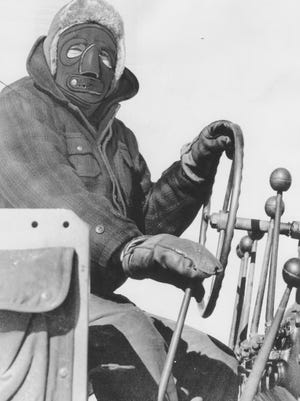 An unidentified worker at Portsmouth Air Force Base wears a face mask against the cold aboard a road grader in January 1956.