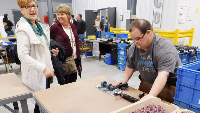 Sandco Industries employee Michael Garcia shows his mother Lois Garcia, left, and Whirlpool Corp. employee Susan Damschroder, what he does at the new plant when it opened in Clyde in 2017.