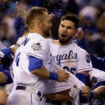Kansas City Royals' Eric Hosmer is congratulated by teammates after hitting the game-winning sacrifice fly during the 14th inning of Game 1 of the Major League Baseball World Series against the New York Mets Wednesday, Oct. 28, 2015, in Kansas City, Mo. The Royals won 5-4 to take a 1-0 lead in the series. (AP Photo/David J. Phillip)