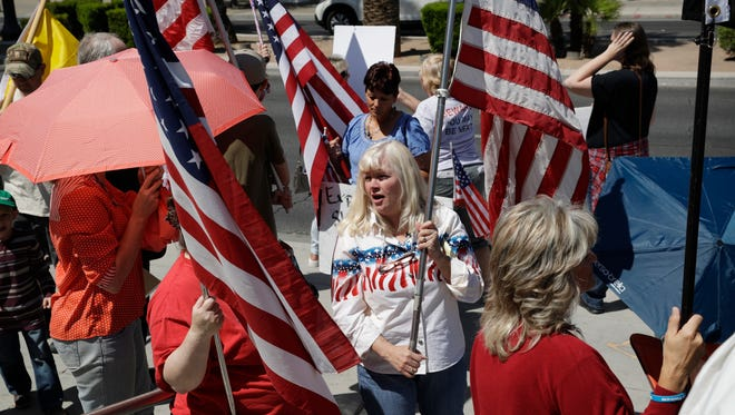 People rally in support of defendants on trial at a federal courthouse, on  April 10, 2017, in Las Vegas. Protesters gathered outside the courthouse in support of six defendants accused of wielding weapons against federal agents during a 2014 standoff involving cattleman and states' rights advocate Cliven Bundy.