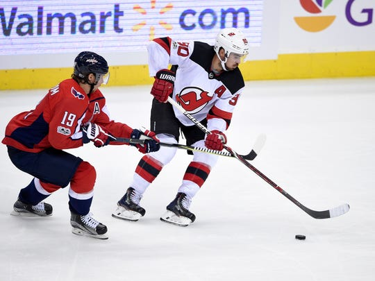 Washington Capitals center Nicklas Backstrom (19), of Sweden, battles for the puck against New Jersey Devils center Marcus Johansson (90), of Sweden, during the third period of an NHL preseason hockey game, Wednesday, Sept. 27, 2017, in Washington. The Devils won 4-1. (AP Photo/Nick Wass)