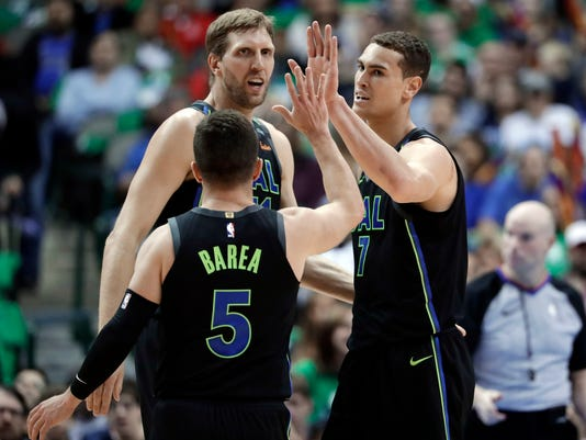 Dallas Mavericks guard J.J. Barea (5), center Dwight Powell (7) and center Dirk Nowitzki (41) celebrate a basket by Powell during the first half of an NBA basketball game against the Denver Nuggets in Dallas, Tuesday, March 6, 2018. (AP Photo/Tony Gutierrez)