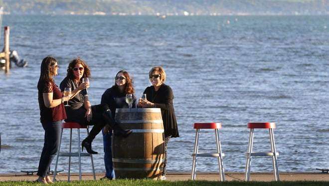 Adena Miller, left, and friends Amy Begy, Carrie Ritter and Susan Senice enjoy a cocktail along the shoreline of Canandaigua Lake at The Inn on the Lake.