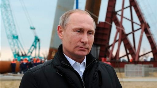 Russian President Vladimir Putin, via a video link,  addresses people marking the second anniversary of Russia's annexation of Crimea in Moscow's Red Square, as he visits the construction site of the Kerch Strait bridge on the Tuzla Island, Crimea, Friday, March 18, 2016. Russian President Vladimir Putin travelled to Crimea on Friday to mark the second anniversary of the peninsula's annexation and inspect construction of a bridge meant to link it to mainland Russia.  (Mikhail Klimentyev/Sputnik, Kremlin Pool Photo via AP)