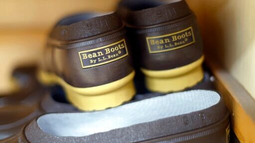 FILE - This Aug. 17, 2017 file photo shows a pair of boots being constructed at the L.L. Bean manufacturing center in Lewiston, Maine. L.L. Bean is moving further away from its original model of direct-to-customer catalog sales and sales in their own stores, with an agreement in 2020 to sell products through Nordstroms, Staples and the Scheels sporting goods chain.
