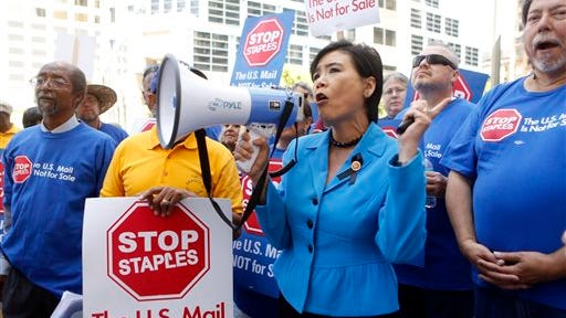 U.S. Congresswoman Judy Chu, D-Calif., joins U.S. Post Office employees during a protest outside a Staples store, Thursday in downtown Los Angeles. Postal workers around the country protested in front of Staples stores on Thursday, objecting to the U.S. Postal Service's pilot program to open counters in stores, staffed with retail employees.