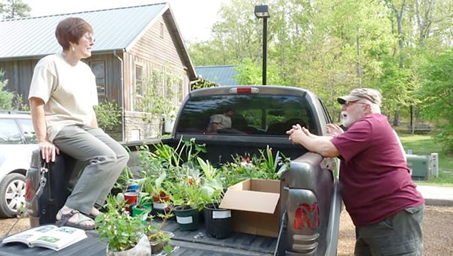"""Friends of Bowie Nature Park members Rene Cashion and Bob Brooks engage in """"garden talk"""" at last year's plant swap."""