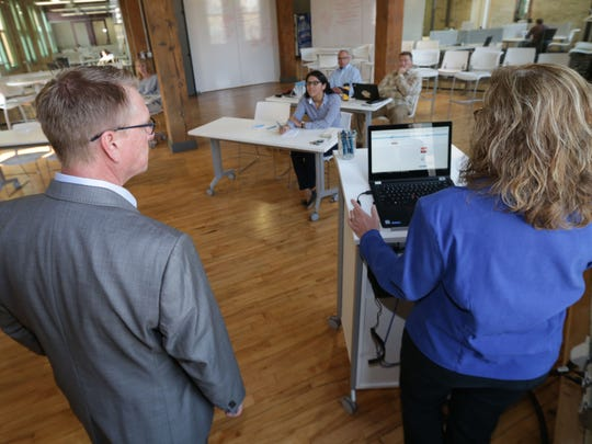 "Ray Seaver (left), founder and CEO of Zizzl, a company that manages payroll and benefits for other companies, and Loree Swartzendruber, an account executive with Zizzl, give a demonstration of the ""Ask Emma"" tool, which walks users through selecting health care plans."