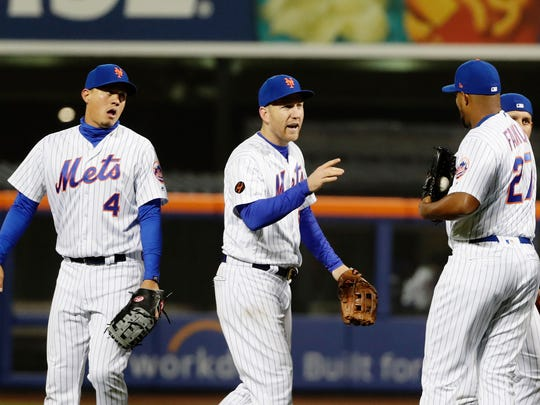 New York Mets' Todd Frazier, center, celebrates with teammates Wilmer Flores (4) and relief pitcher Jeurys Familia (27) after a baseball game against the Philadelphia Phillies Tuesday, April 3, 2018, in New York. The Mets won 2-0. (AP Photo/Frank Franklin II)