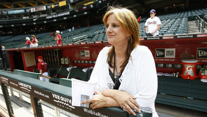 Paola Boivin stands in the Diamondbacks dugout while covering Arizona's season opener in 2012.