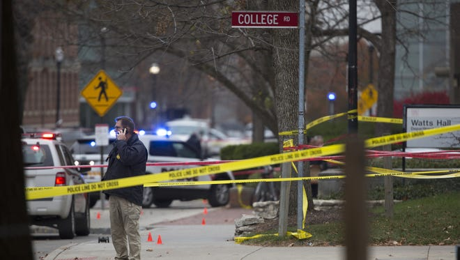 Investigators work the scene outside of Watts Hall on Ohio State's campus where police say a man attacked pedestrians with a vehicle and a butcher knife.