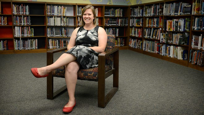 """Jenna Kimlinger, a seventh grade social studies teacher at Clyde A. Erwin Middle School, sits in the library on Thursday. Kimlinger, who has been teaching at the school for three years, will not be entitled to earn tenure. """"We will continue to fight the good fight,"""" Kimlinger said about the issue."""