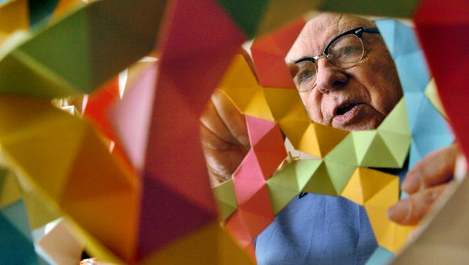 In a photo from 2007, Magnus Wenninger, who died Friday, Feb. 17, at the age of 97, looks at one of the thousands of polyhedron models he has constructed in his lifetime.