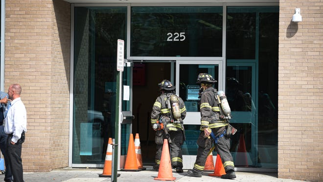 Two firefighters enter into the Center for Student Success - Passaic County Community College, where an odor was reported in Paterson on 9/21/17.