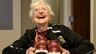 Sister Jean the 98-year-old chaplain of the Men's Basketball Team holds athletic shoes that the basketball team gave to her at Loyola University Chicago on March 20, 2018.