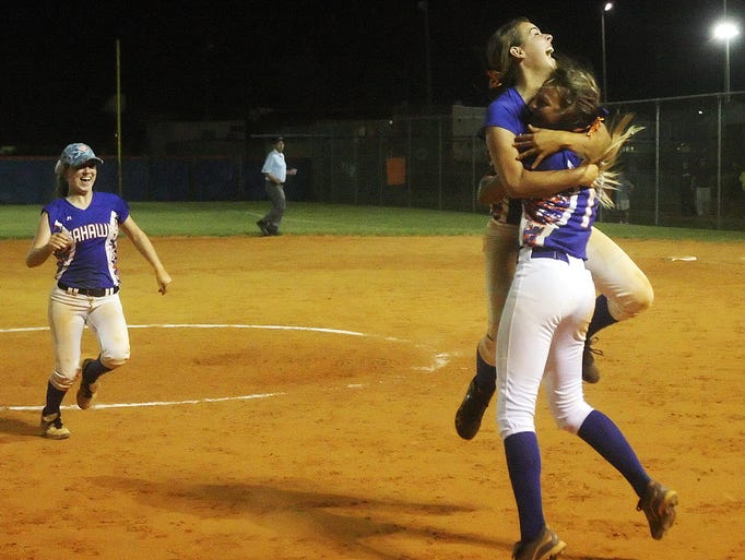 Cape Coral High School's Kerry McLaughlin leaps into the arms of Makenzie Buss to celebrate beating Lemon Bay on Thursday at Cape Coral High School.