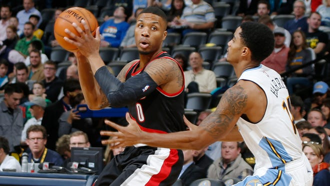 Portland Trail Blazers guard Damian Lillard, left, looks to pass the ball as Denver Nuggets guard Gary Harris, right, defends in the first half of an NBA basketball game Monday, Nov. 9, 2015, in Denver.