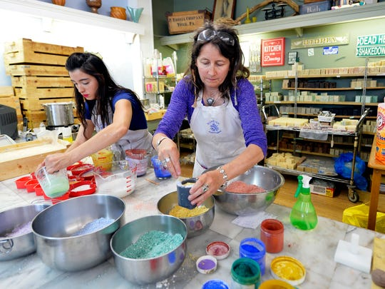 Sunrise Soap Company owner Christina Clarke, center, and assistant Ariel Linebaugh make rainbow-themed soaps at the store in York in 2014. This holiday season, 'bath bombs' are a popular selling item, Clarke said.