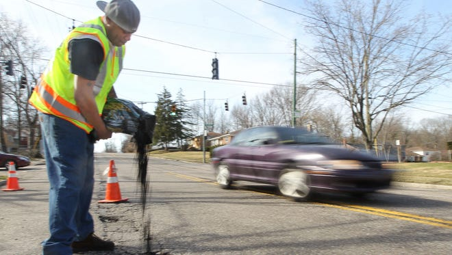 Mark Johnson, a worker for the city of Cincinnati, pours asphalt patch filler into a pothole on Daly Road in Finneytown Monday.