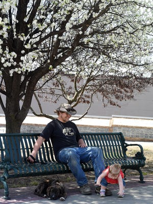 Joe Denzer of rural Baxter County, enjoys a shady spot Tuesday, March 31, 2015, at the Mountain Home Veterans Plaza with his one-year-old daughter, Brooklyn Denzer and his puppy, Ruger.