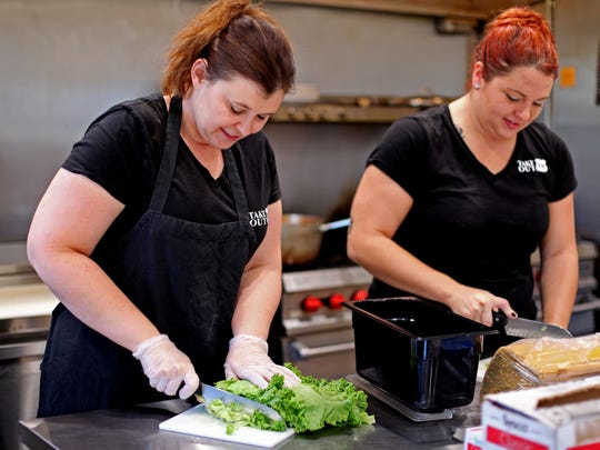 Pam Fitzgerald, left, owner of Take Out 250 in Fisherville, along with manager Lacey Marshall, prepare salads at the restaurant located along U.S. 250 on Tuesday, Sept. 13, 2016.