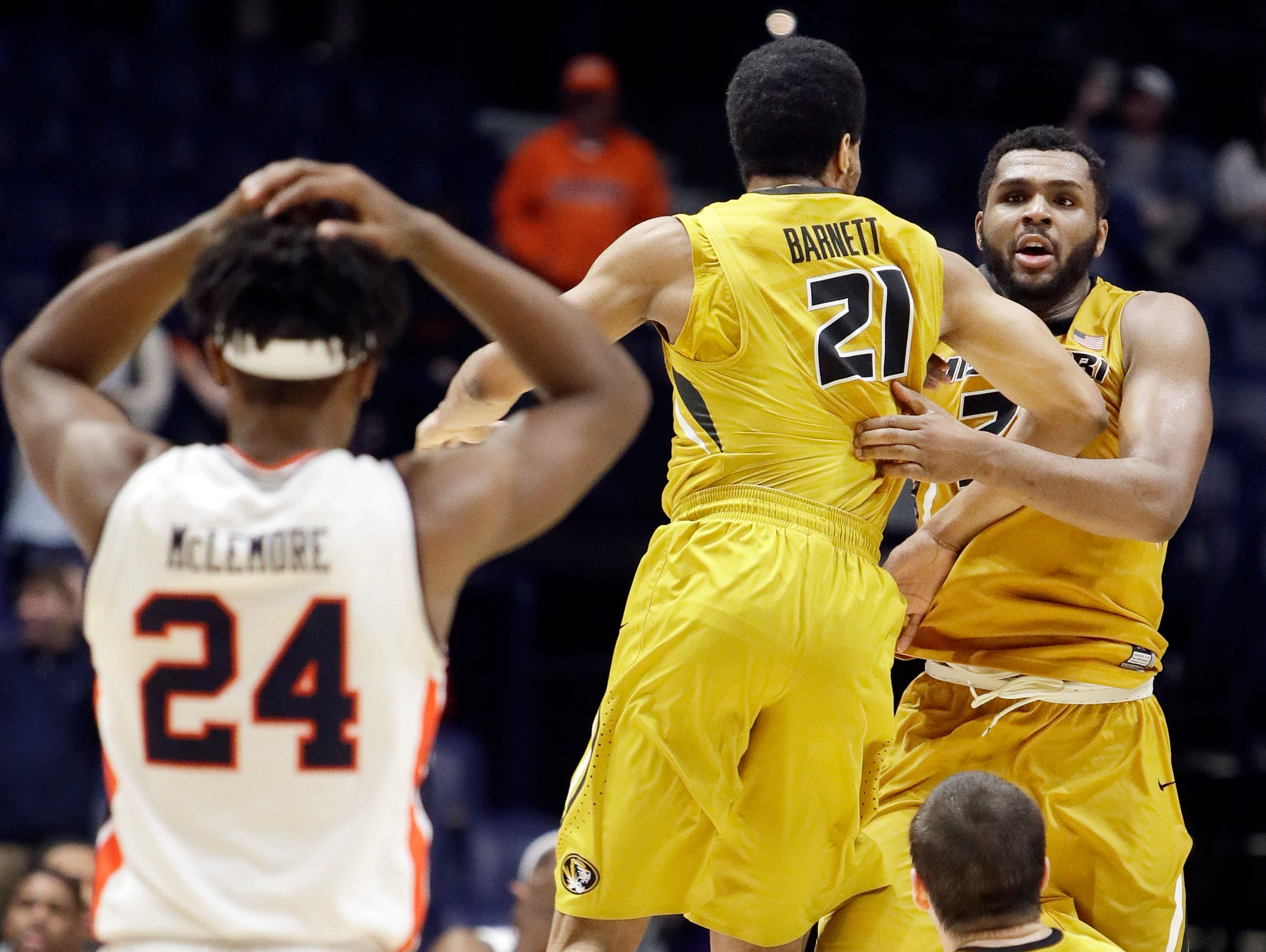 Missouri forward Kevin Puryear, top right, celebrates with Jordan Barnett (21) after Puryear hit a 3-point basket to give Missouri a 86-83 win over Auburn in overtime of an NCAA college basketball game at the Southeastern Conference tournament Wednesday, March 8, 2017, in Nashville, Tenn. At left is Auburn forward Anfernee McLemore.