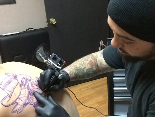Adam Ryan starts the outline of a tattoo for his younger