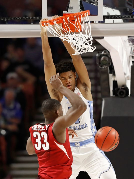North Carolina's Isaiah Hicks (4) dunks against Arkansas' Moses Kingsley (33) during the second half in a second-round game of the NCAA men's college basketball tournament in Greenville, S.C., Sunday, March 19, 2017. (AP Photo/Chuck Burton)