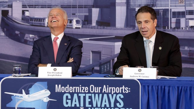 New York Gov. Andrew Cuomo, joined by Vice President Joe Biden, left, speaks in a hangar of the Vaughn College of Aeronautics and Technology, in New York,  Monday, Oct. 20, 2014, during a presentation to discuss the need to improve New York's airports. Cuomo announced a design competition to modernize and improve New York City's John F. Kennedy and LaGuardia Airports. (AP Photo/Richard Drew)