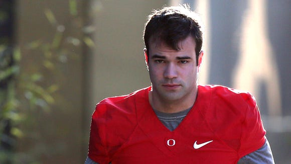 Jeff Lockie (17) is one of five quarterbacks fighting for Marcus Mariota's position on the Oregon football team. He walks to the Hatfield-Dowlin outdoor fields on Tuesday, March 31, 2015 in Eugene, Ore.