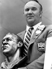 Doug Atkins holds a bust of himself after being inducted into the National Pro Football Hall of Fame in Canton, Ohio, on Aug. 6, 1982.