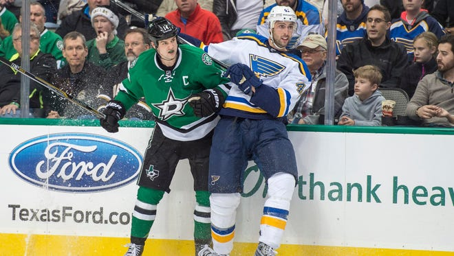 Dallas Stars left wing Jamie Benn (14) checks St. Louis Blues defenseman Robert Bortuzzo (41) during the third period at the American Airlines Center. The Stars shut out the Blues 3-0.