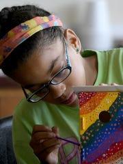 Nevaeh Trammell, 10, paints a bird house Wednesday