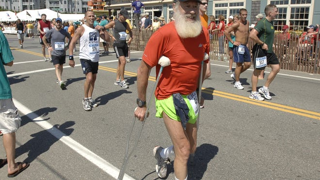 Suffering from severely sprained ligaments in his foot, Brian Salzberg crosses the finish line of the 2008 Falmouth Road Race on crutches. Salzberg planned a knee replacement around this year's race, but like everyone else, he'll have to settle for a virtual event necessitated by the coronavirus pandemic.