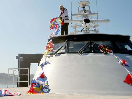 Kitsap Transit deckhand Jim Loria the gathers decorations before Rich Passage departed on a sailing for elected officials and dignitaries on Wednesday.