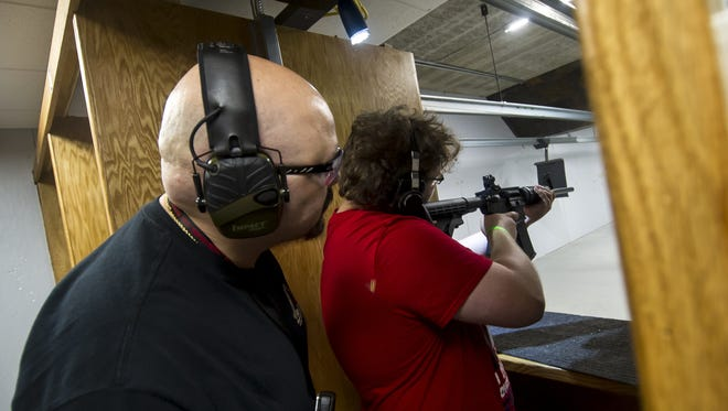 Ed Cabrera, Firearms Trainer, left, looks on as Sebastian Mongeau of Lacey, fires a Smith & Wesson Sport AR-15 during a free firearms training at the Union Hill Gun Club in Monroe Twp. on May 20, 2018.