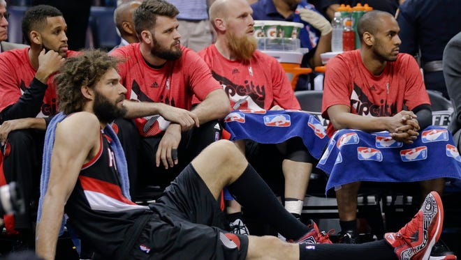 Portland Trail Blazers center Robin Lopez sits on the floor as players watch the final minutes of the second half of Game 5 of an NBA basketball Western Conference playoff series against the Memphis Grizzlies Wednesday, April 29, 2015, in Memphis, Tenn. The Grizzlies won 99-93 to win the series 4-1.