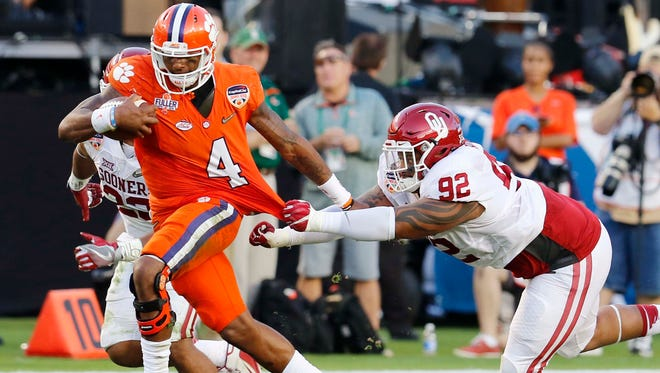 Clemson quarterback Deshaun Watson (4) runs with the ball as Oklahoma defensive tackle Matthew Romar (92) attempts to stop him, during the first half of the Orange Bowl NCAA college football semifinal playoff game, Thursday, Dec. 31, 2015, in Miami Gardens, Fla.