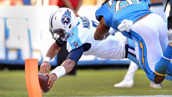 Tennessee Titans quarterback Marcus Mariota (8) dives in for a third-quarter touchdown as San Diego Chargers free safety Dwight Lowery (20) defends at Qualcomm Stadium.