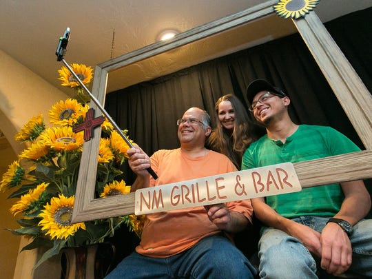 Frank Tawney left, Lindsey McDonald, center, and Ralph Diaz pose for a photograph on Wednesday in front of the selfie wall at NM Grille & Bar, formerly Meson de Mesilla. Guest will be able to take pictures there for a chance to win a $50 restaurant gift card.