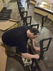 Mike Hotelling installs the standards, the parts that make up the frame for the 806 new seats, Thursday in the balcony at the Paramount Theatre.