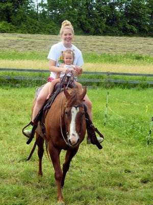 "Bunny, the quarter horse, with owner Regan Howard's daughter, Jenna Howard, and her granddaughter, Tarah Carten, in an undated photo. Howard advocates helmets. She said this was a ""short jaunt."" Barre police are seeking information related to Bunny's death."
