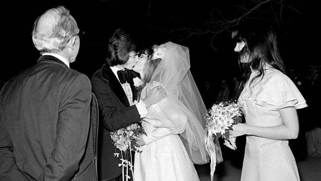 """With the Rev. Arnet Gregory, left, looking on, the groom, Steve Sutton, kisses the bride, Pam Hassell, in the snow as the bridemaid Linda Bennette looks on Jan. 20, 1978. """"We thought it would be neat and different,"""" explained the groom. """"Anyhow, we've waited this long – we're not going to let a little snow stop us now."""""""