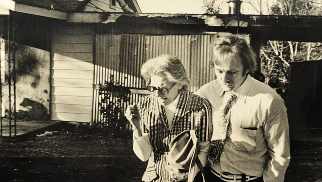 Teresa Hunt, member of the Pensacola-Escambia Human Relations Committee and the school board's Citizens Advisory Committee, cries as she and Alain Hebert examine the charred remains of her home on Feb. 22, 1976. The fire was caused by arson and believed to be a result of the Escambia High School racial controversy.