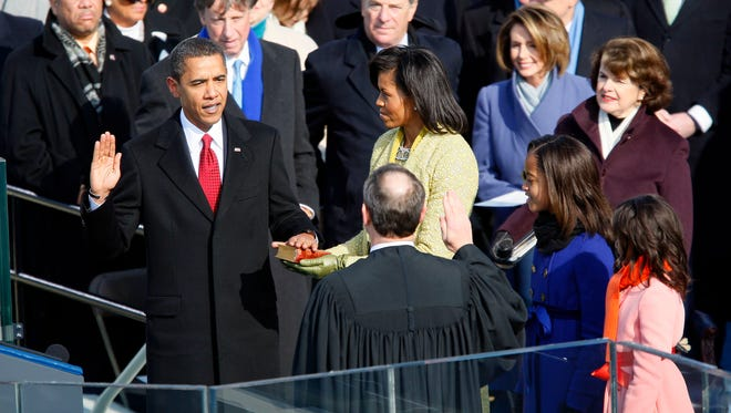 Barack Obama, left, takes the oath of office as the 44th U.S. President from Supreme Court Chief Justice John Roberts on the West Front of the U.S. Capitol in Washington, D.C., Tuesday, January 20, 2009.