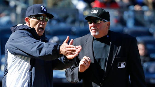New York Yankees manager Joe Girardi, left, protests to home plate umpire and crew chief Dana DeMuth that Houston Astros shortstop Carlos Correa stayed from the base path and onto the field while running out an infield grounder and blocking Dellin Betances's throw for the put out in the eighth inning of an opening day baseball game in New York, Tuesday, April 5, 2016. Houston Astros Jose Altuve scored the go-ahead run on the play in the Yankees 5-3 loss to Houston. (AP Photo/Kathy Willens)