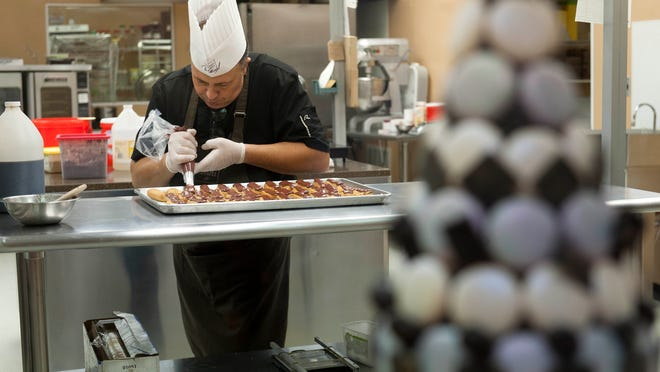 Pastry chef Frederic Crepin tops eclairs in the kitchen of chocolatier Michel Cluizel in West Berlin, Berlin Township.  The facility uses chocolate shipped from Cluizel headquarters in France to make confections for clients around the U.S.