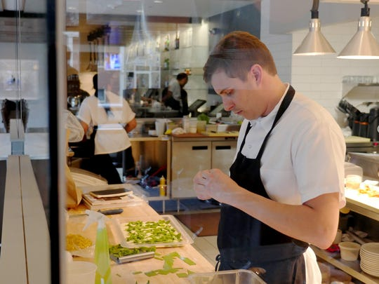 Executive Chef Nick Janutol works in the glass-enclosed