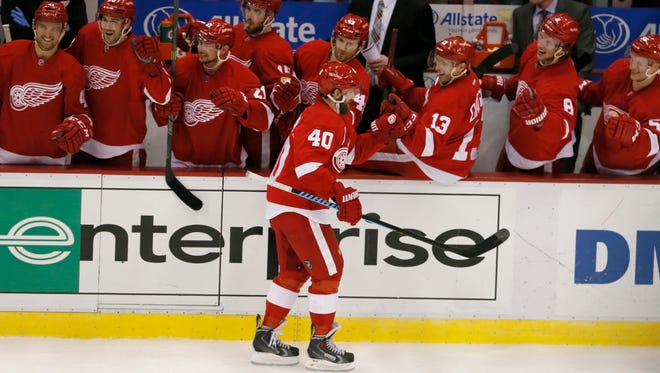 With hats laying on the ice, the Detroit Red Wings congratulate Henrik Zetterberg after Zetterberg scored his third goal for a natural hat trick and a 6-4 lead over the Buffalo Sabres in the third period on Jan.18, 2015 in Detroit.